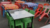 terrível : Conventional plastic tables and chairs in one of the cheapest cafes in Asia. Multicolored polyethylene tablecloths on plastic tables on the street. Tables chairs and plastic Stock Footage