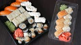 sashimi : Two large sushi sets with lots of sushi, roll, maki, nigiri, gunkan. Stylish sushi sets on black wooden table