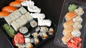 сакэ : Two large sushi sets with lots of sushi, roll, maki, nigiri, gunkan. Stylish sushi sets on black wooden table