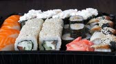 сакэ : Camera zooms stylish fresh sushi set with various kinds of sushi rolls, close up