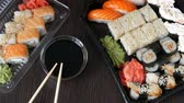 сакэ : Big sushi set with variety of sushi rolls, maki, nigiri, gunkan on a stylish dark background. Soy sauce and bamboo chopsticks lie nearby