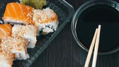 different kinds : Camera zooms. Stylishly laid sushi set on a black wooden background next to soy sauce and Chinese bamboo sticks. Various sushi rolls with salmon, eel, cucumber shrimps and other various stuffing Stock Footage