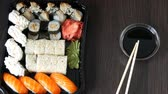 different kinds : Stylishly laid sushi set on a black wooden background next to soy sauce and Chinese bamboo sticks. Various sushi rolls with salmon, eel, cucumber shrimps and other various stuffing