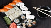 сакэ : Large sushi sets with lots of sushi, roll, maki, nigiri, gunkan. Stylish sushi sets on black wooden table next to soy sauce and Chinese sticks
