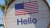 registrar : Beautiful sign with American flag with the inscription Hello in English. Sign with the words hello Vídeos