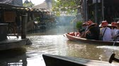улов : People are swimming in a boat on a brown river in Thailand in the haze. Walking people along the shore and riding on river in a boat. Pattaya Floating Market