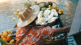 wędkarz : PATTAYA, THAILAND - December 18, 2017: The seller of exotic fruits on a boat and a straw hat sails on the river in Thailand, on floating market, Pattaya Wideo