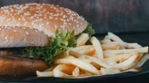 barbequed : Big burgers on plate next to a french fries
