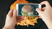 real jam : Female hands make smartphone photo of a large burger on a plate. Photo of fast food