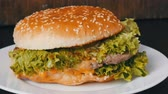 majonéz : Large triple burger with lettuce leaves on a white plate. Hamburger on a stylish wooden background. Fast food
