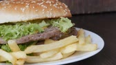 batatas fritas : Large triple burger with lettuce leaves and French fries on a white plate. Hamburger on a stylish wooden background. Fast food