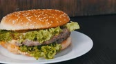 szolgáló : Large triple burger with lettuce leaves on a white plate. Hamburger on a stylish wooden background. Fast food