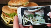 make photo : Female hands make smartphone photo of a large burger on a plate. Photo of fast food