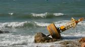 буй : Large yellow buoy on the shores of azure sea. The waves hit the buoy and the big rocks on the shore Стоковые видеозаписи