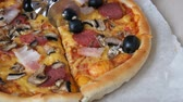 древесный : Hand cut a piece of a Big Italian pizza with black olives, bacon, salami and cheese close up