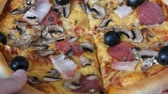 salam : Hand take a piece of a Big Italian pizza with black olives, bacon, salami and cheese close up
