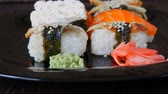 different kinds : Stylish black sushi set on flat plate with different kinds of roll, nigiri, maki, gunkan. Japanese national cuisine close up view