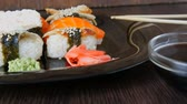 chopstic : Stylish black sushi set on flat plate with different kinds of roll, nigiri, maki, gunkan. Japanese national cuisine