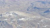 keskeny kilátás : Mountain landscape with snow-capped peaks, view from airplane Stock mozgókép