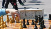 епископ : April 21, 2018 - Kamenskoye, Ukraine: Children play chess in street. Street Chess Tournament outdoor, chess clock presses the hand