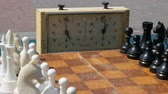checkmate : April 21, 2018 - Kamenskoye, Ukraine: Black and white chess stand on the board, next to a vintage chess clock on street