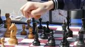 шах и мат : April 21, 2018 - Kamenskoye, Ukraine: Children play chess in street. Street Chess Tournament outdoor, chess clock presses the hand