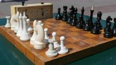 bishop : Black and white chess stand on the board, next to a vintage chess clock on street