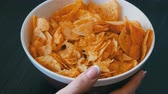preguiçoso : Large plate with potato chips on the table. Female hands with beautiful manicure take chips