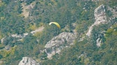 planeur : Yellow paraglider flies against a background of green rocky Crimean mountains