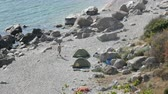 kids tent : Rocky coast of the Black Sea on which there are few people with tents. Camping in wild places