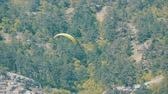 glides : Yellow paraglider flies against a background of green rocky Crimean mountains