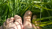 feel : Female legs in the sand against background of green grass