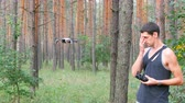 transmissor : Cute tall man launches drone or quadrocopter in the woods