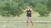 multicopter : Cute tall man launches and holds a drone or quadrocopter in the woods Stock Footage