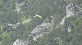 adrenaline : Yellow paraglider flies against a background of green rocky Crimean mountains