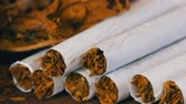 Close up od homemade cigarettes or roll-up next to dry tobacco leaves stuffed with chopped tobacco