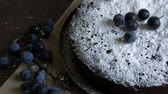 pudding dishes : Chocolate cake brownie generously covered with powdered sugar stylishly lying next to the blue berries