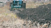 kazma : Blue Tractor with four furrow plough plowing field with black soil close up view