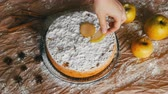 tarte : Female hand puts apple slices on delicious traditional freshly baked homemade gingerbread apple pie Charlotte richly powdered sugar top view Stock Footage