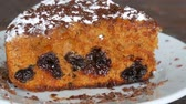flaky : Icing sugar generously sprinkles homemade freshly baked cake with cherry Stock Footage