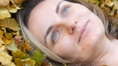 oblečený : Close up portrait of the face of beautiful young girl without makeup who lies in the autumn yellow foliage and enjoys life