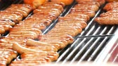 advent roasts : Women grill lot of delicious fresh German sausages. A large number of Nuremberg sausages near fresh buns are prepared on the Christmas food market Stock Footage