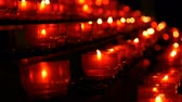 Row of christian prayer red round votive candles burn in the dark. Prayer lighting Sacrificial Candles close up view. Burning memorial candles in Catholic church. Celebrating christmas in Cathedral Stock Footage