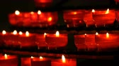 inexpensive : Row of christian prayer red round votive candles burn in the dark. Prayer lighting Sacrificial Candles close up. Burning memorial candles in Catholic church. Celebrating christmas in Cathedral