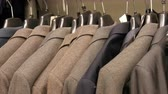 garment : A row of warm mens jackets on a hanger at a mens clothing store in mall. Various mens suits hanging in the shopping center