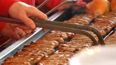 lokanta : Women grill lot of delicious fresh German sausages. A large number of Nuremberg sausages near fresh buns are prepared on the Christmas food market Stok Video