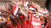 humorous : New Year and Christmas hoops on the head in the form of deer in Santa claus hats and bell in the ear close up view. The spirit of Christmas and New Year