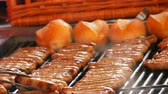 adwent : Women grill lot of delicious fresh German sausages. A large number of Nuremberg sausages near fresh buns are prepared on the Christmas food market Wideo