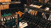 butik : Stylish clothes hanging in row on hangers in a clothing store in a mall. Wideo