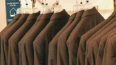 hésiter : Number of identical-colored mens suits hanging on a hanger in a clothing store in a mall Vidéos Libres De Droits